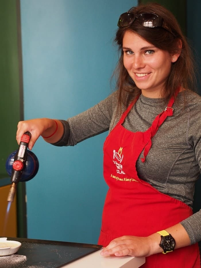 Learning how to make crème brûlée at a cooking class in Paris