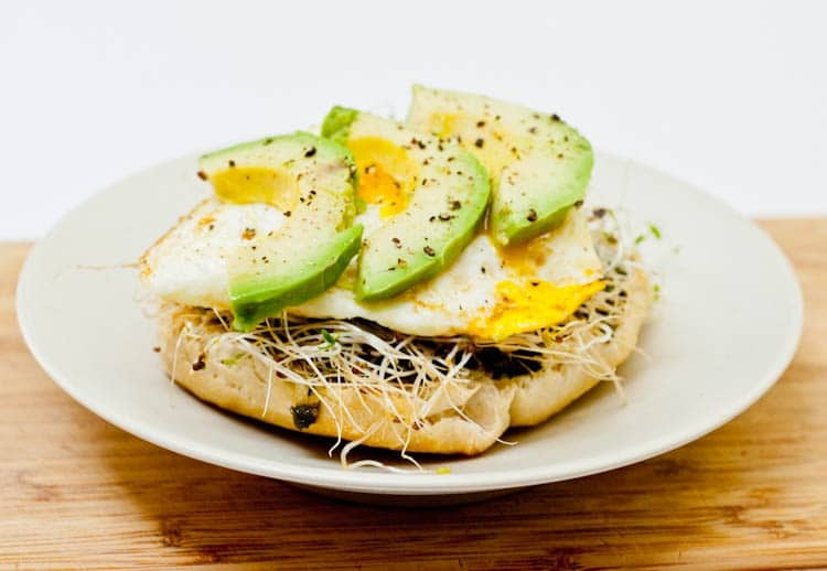 english muffin with eggs, avocado, pesto and alfalfa sprouts