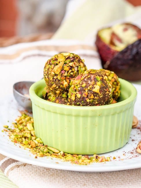 Five ingredient sweet, rich and smooth honey avocado truffles with pistachios, tahini and cocoa powder. Simply irressitible and practically healthy. A guilt free holiday treat. Gluten Free and Dairy Free too.