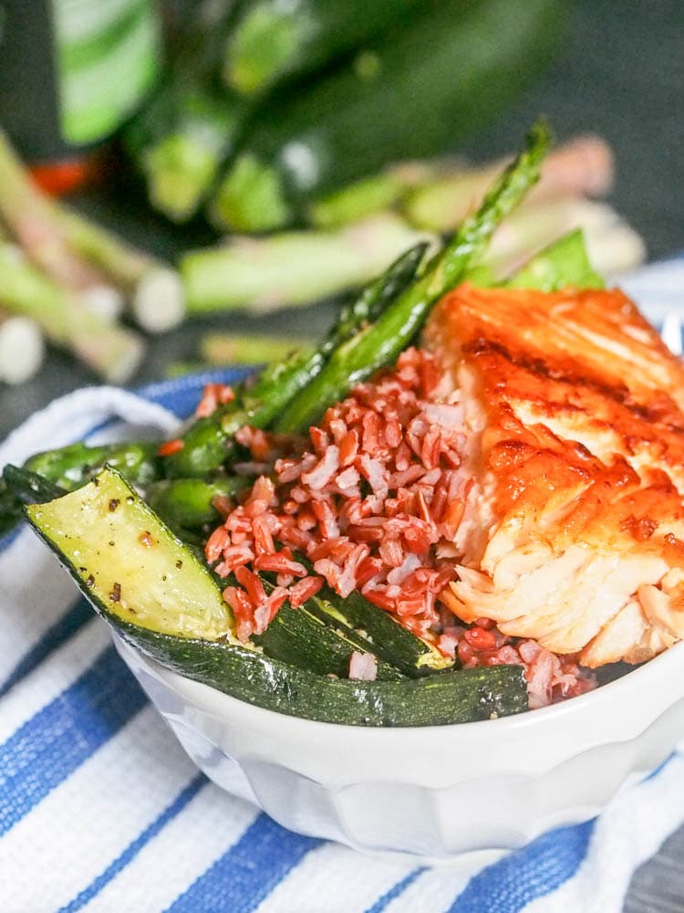 Salmon, red rice veggie bowls with roasted red pepper sauce are the ultimate feel good dinner meal. Think hearty rice, topped with soft tender salmon, roasted asparagus and zucchini and drizzled with a creamy tahini roasted red pepper sauce. Gluten Free and Dairy Free. | avocadopesto.com