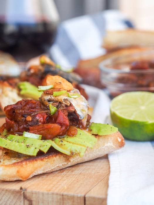 Sardine Toast with avocado, tomato relish and garlic chips makes for a perfect summer lunch or light dinner. Inspired by Portuguese cuisine, a must try, super hearty healthy and omega 3 loaded dish. Gluten Free + Dairy Free | avocadopesto.com