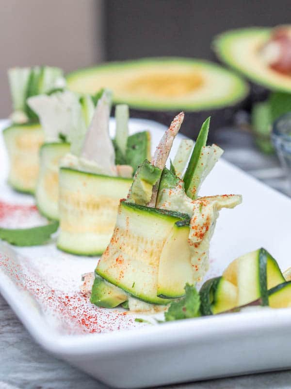 Super light and refreshing 20 minute 6 ingredient low carb zucchini rolls with hummus, chicken, cucumber, mint and avocado make for the perfect party appetizer or light meal. Gluten Free + Dairy Free too. | avocadopesto.com