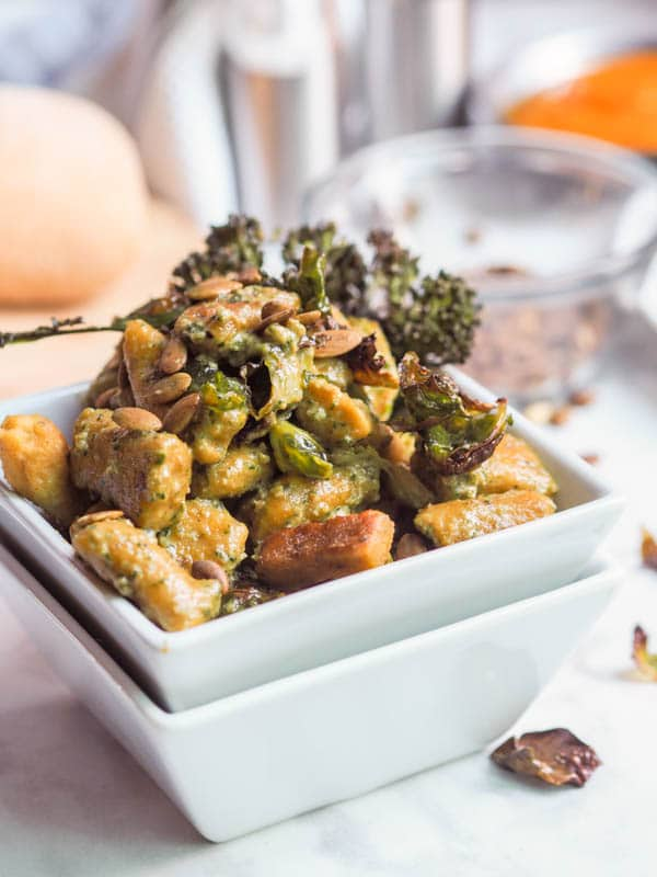4 ingredient vegan and gluten free pumpkin gnocchi served with vegan basil pesto, oven roasted broccoli, brussels sprouts and pumpkin seeds. Perfect winter dinner.