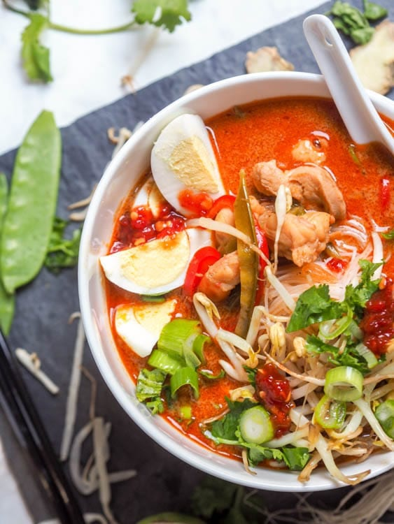 Shrimp and Chicken Laksa soup- A malaysian style soup with a creamy coconut milk base and incredible depth of flavors thanks to ginger, fish sauce, lemongrass and other spices. One of my all time favorite soup recipes by far!