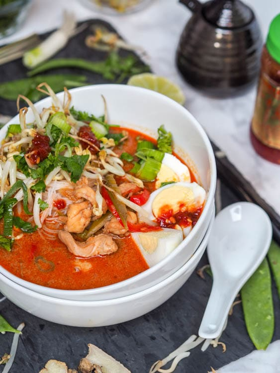 Shrimp and Chicken Laksa soup- A malaysian style soup with a creamy coconut milk base and incredible depth of flavors thanks to ginger, fish sauce, lemongrass and other spices. One of my all time favorite soup recipes by far! Don't be deterred by the long ingredient list!