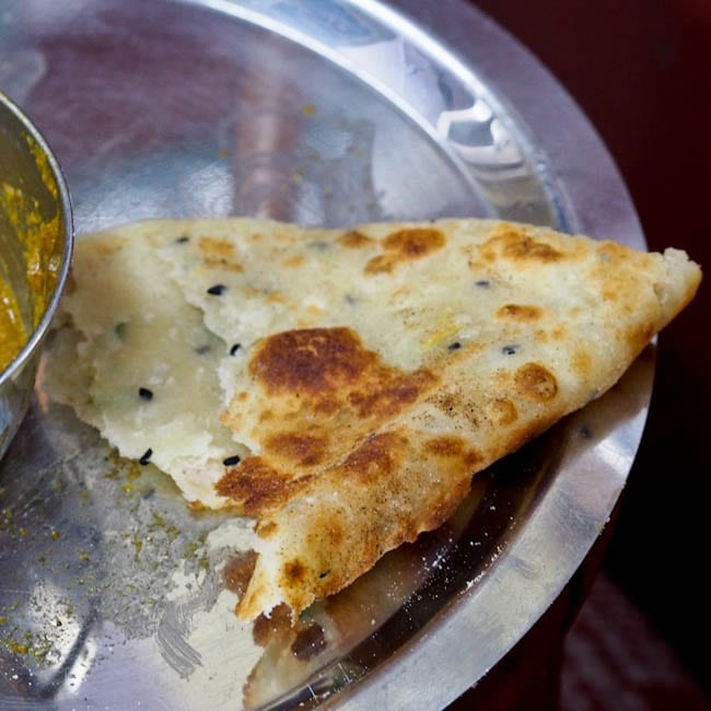 A piece of garlic naan on a plate