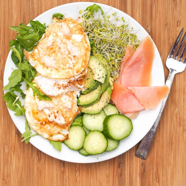 salmon and eggs breakfast plate with avocado, cucumbers, alfalfa, and arugula