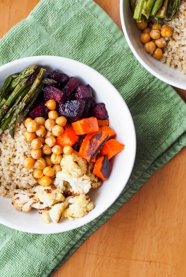 Vegan quinoa bowl layered with roasted asparagus, cauliflower, beets, squash and chickpeas