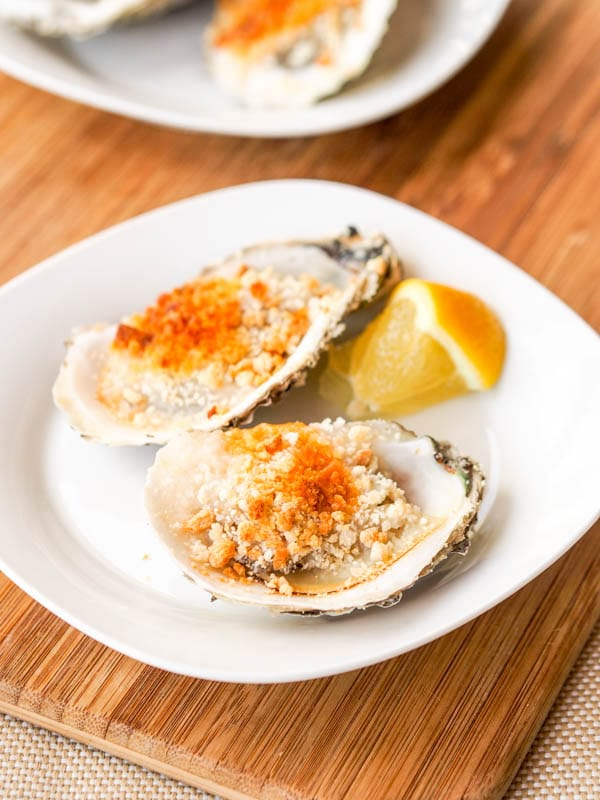 Baked oysters served with a lemon wedge