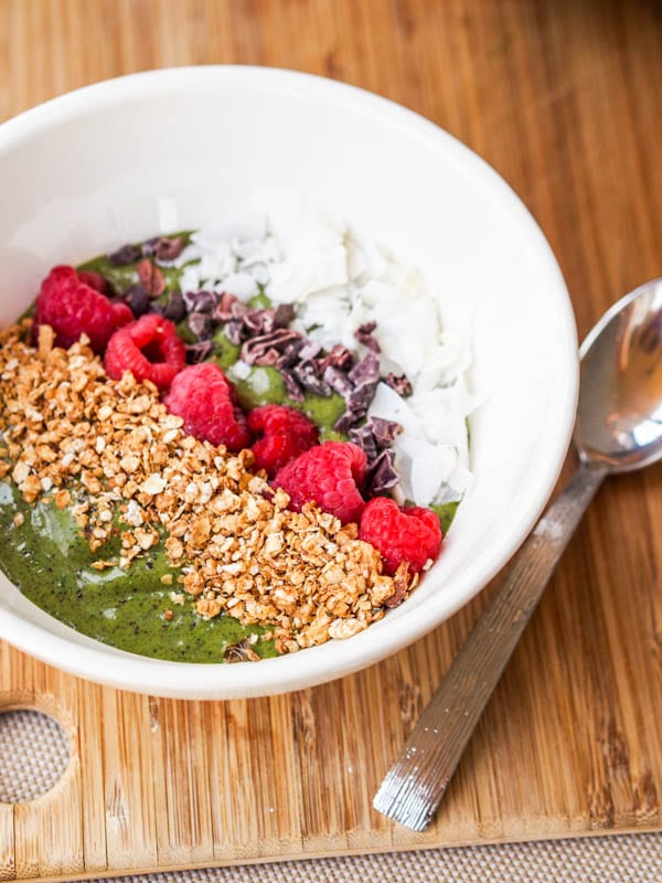 Green Smoothie Bowl topped with granola, raspberries, cacao nibs and coconut flakes