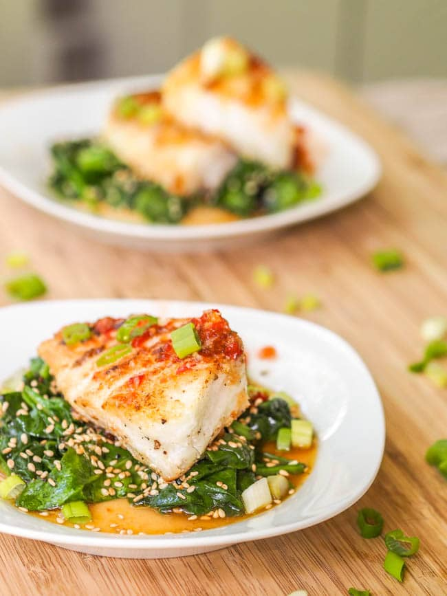 Chilean Sea Bass recipe served over sesame spinach and drizzled with a Vietnamese sauce