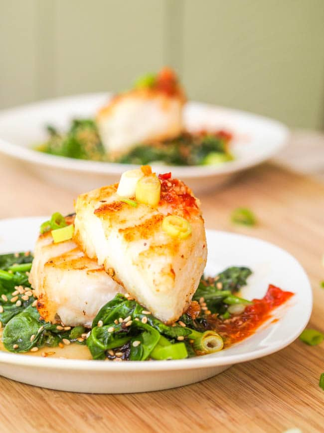 Chilean Sea Bass recipe served over sesame spinach and drizzled with a spicy Vietnamese sauce