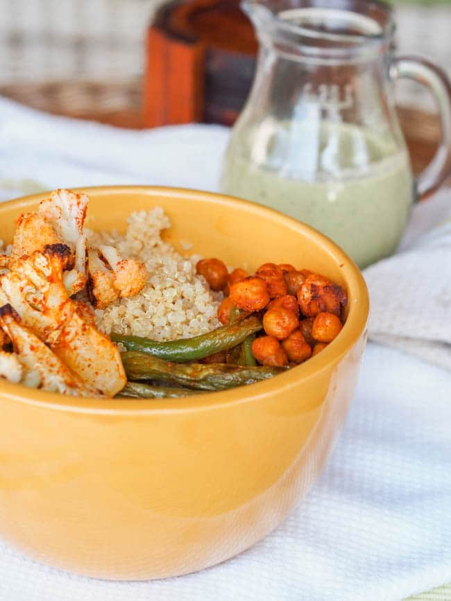 Vegan Quinoa Roasted Veggie Buddha Bowls are brimming with paprika dusted oven roasted cauliflower, green beans and chickpeas. Top that with a garlicky coconut creamy tahini pesto sauce. Meet your new favorite feel good meal. Gluten Free too.