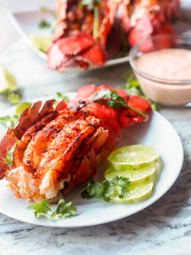 Paprika Broiled Lobster Tail with a size of lime wedges