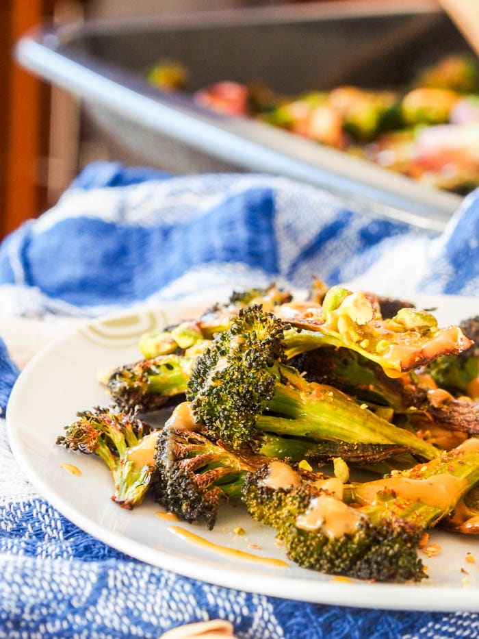 Vegan Roasted broccoli steaks with crushed pistachios and creamy tahini sauce are going to be your new favorite side dish. Crunchy charred broccoli with nutty pistachios and a creamy sauce. Gluten Free too. | avocadopesto.com