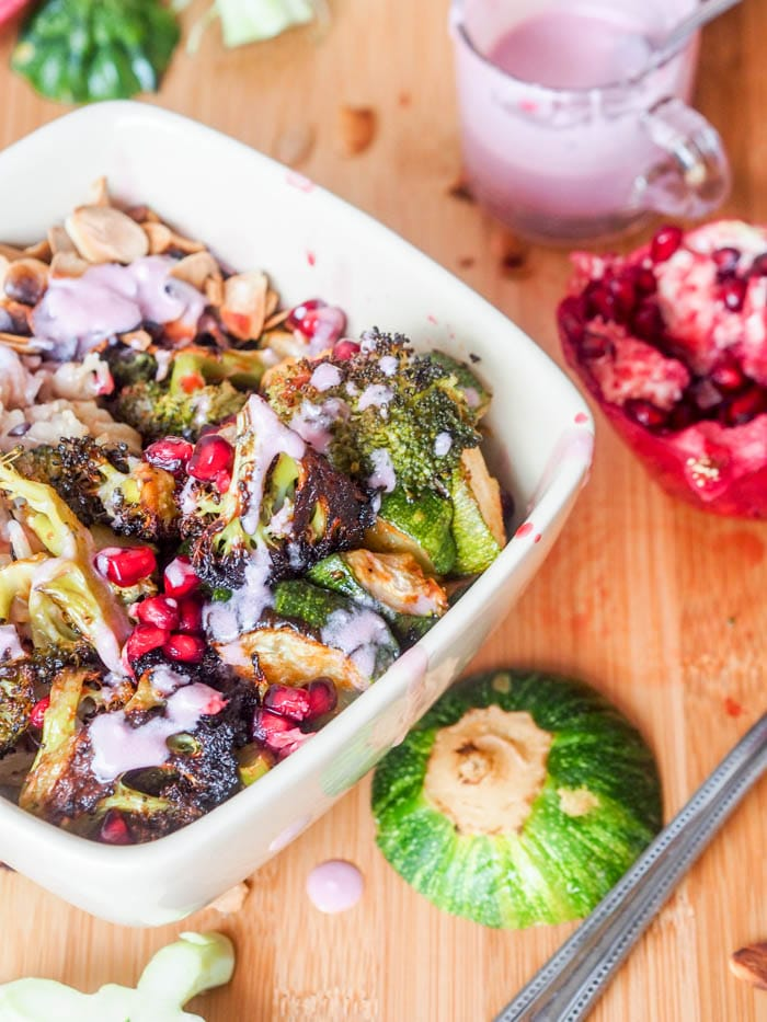 Super colorful and nutrient packed vegan wild rice green bowls with roasted broccoli, and zucchini, toasted almonds, pomegranate arils, and a vibrant pomegranate coconut sauce. Ultimate flavor combination. Easy to make and healthy. Perfect for dinner. Gluten Free too.