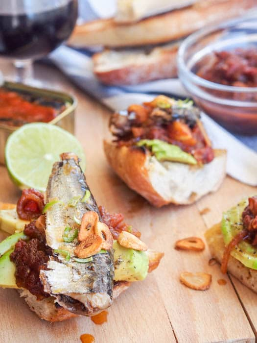 Sardine Toast made with fresh bread topped with avocado slices, tomato relish, canned sardines and garlic chips