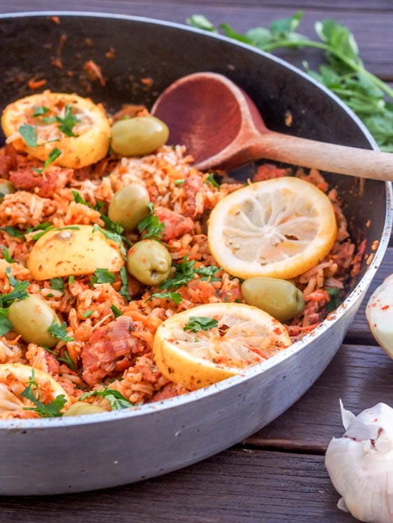one pan mediterranean rice with sausage, lemon and olives in the skillet