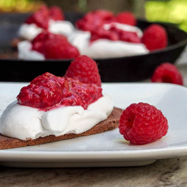 slice of vegan dessert pizza with coconut cream raspberry sauce and a raspberry