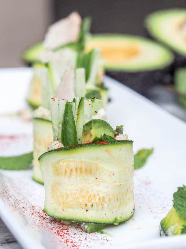 zucchini rolls stuffed with avocado, hummus, cucumber and mint