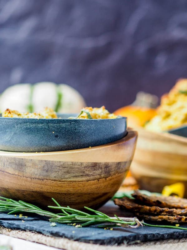 pumpkin dip recipe in wooden and clay bowl with sprig of rosemary
