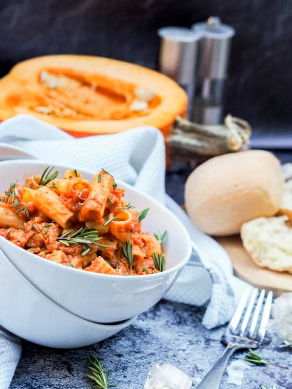 Chicken Bolognese with Pumpkin and Rosemary in a large bowl with fresh bread rolls