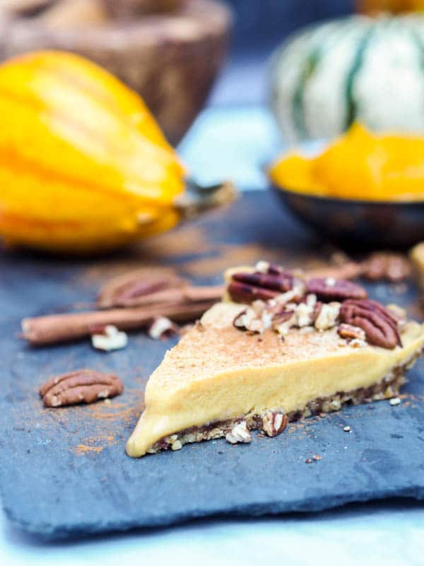 slice of vegan pumpkin pie garnished with pecans