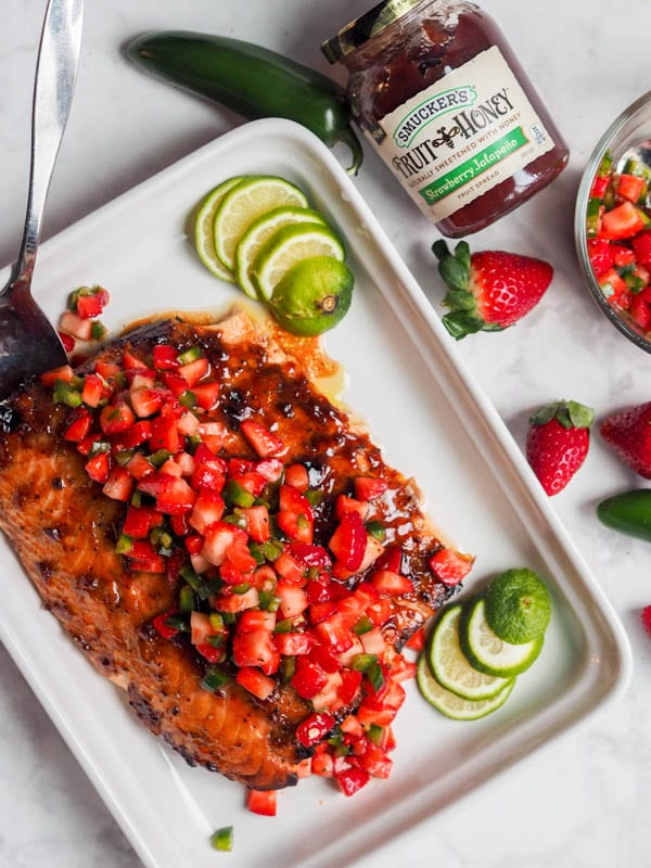 strawberry salmon with jalapeños in a serving dish garnished with lime wedges