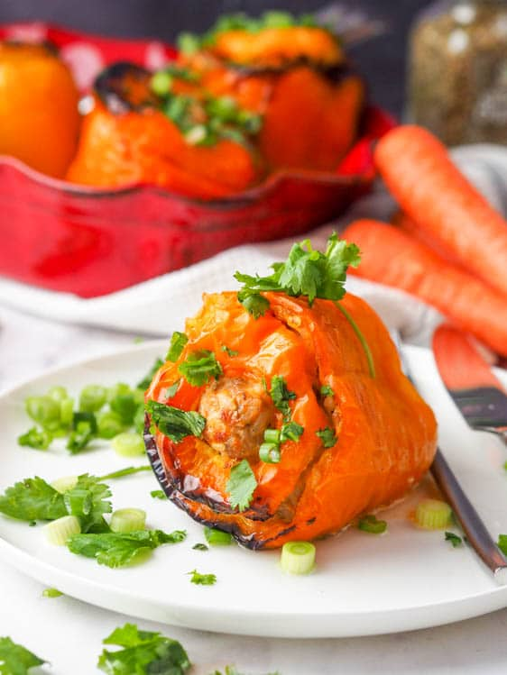chicken stuffed peppers with rice and carrots plated individually
