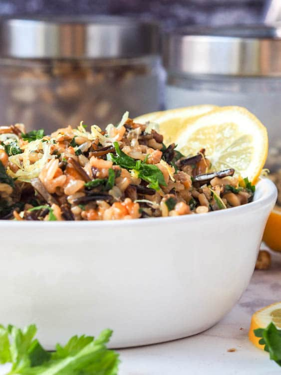vegan wild rice salad with walnuts, lemons, parsley and nutritional yeast in a large bowl with a side of lemon wedges