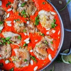 Seven ingredient chicken thighs cooked in a super creamy roasted red pepper sauce with almonds and coconut milk. The ultimate dinner party meal. Easy to make and fit for a crowd. Paleo, Gluten-Free and Dairy-Free.