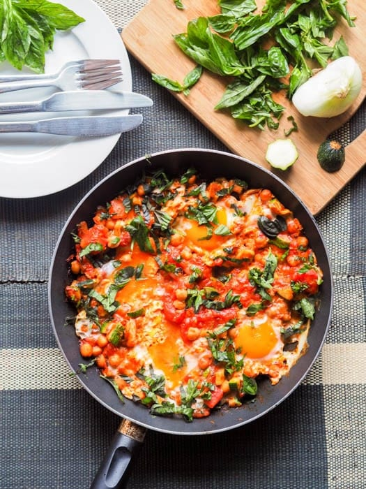 Shakshuka with Eggs, Tomatoes and Chickpeas with additional slivered basil to the side
