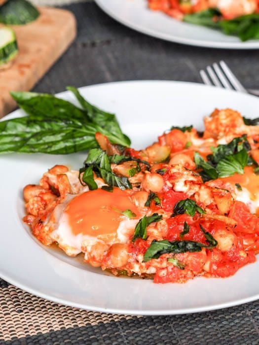 a full plate of Shakshuka with Eggs, Tomatoes and Chickpeas garnished with basil