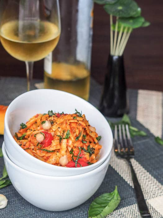 creamy vegan pasta plated with a glass a white wine