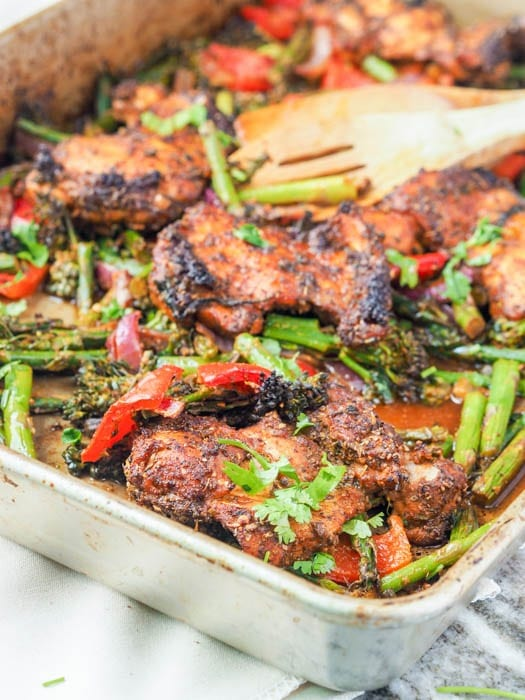broiled chicken thighs and red peppers, broccoli, and asparagus on a baking tray