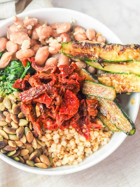 Sorghum Buddha Bowl recipe with zucchini, sun dried tomatoes, cranberry beans, spinach and pumpkin seeds