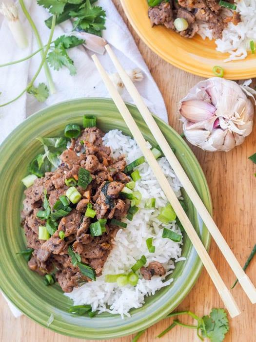Pork Stir Fry plated over rice with chopsticks