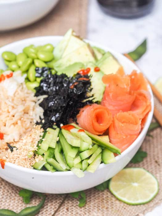 Sushi bowls with smoked salmon, avocado, cucumbers, edamame and rice make for the perfect Japanese themed meal that is ready in under 30 minutes. All the flavors of a sushi roll but none of the fuss. Gluten Free and Dairy Free too.