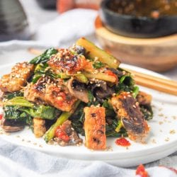 Tempeh Stir Fry makes for an easy Asian themed healthy dinner ready in under 30 minutes. Made with Gailan and mushrooms, topped with a creamy spicy tahini sauce. Gluten Free and Vegan.