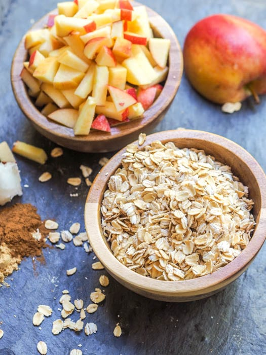 Apple pie oatmeal ingredients with oats and diced apples in bowls