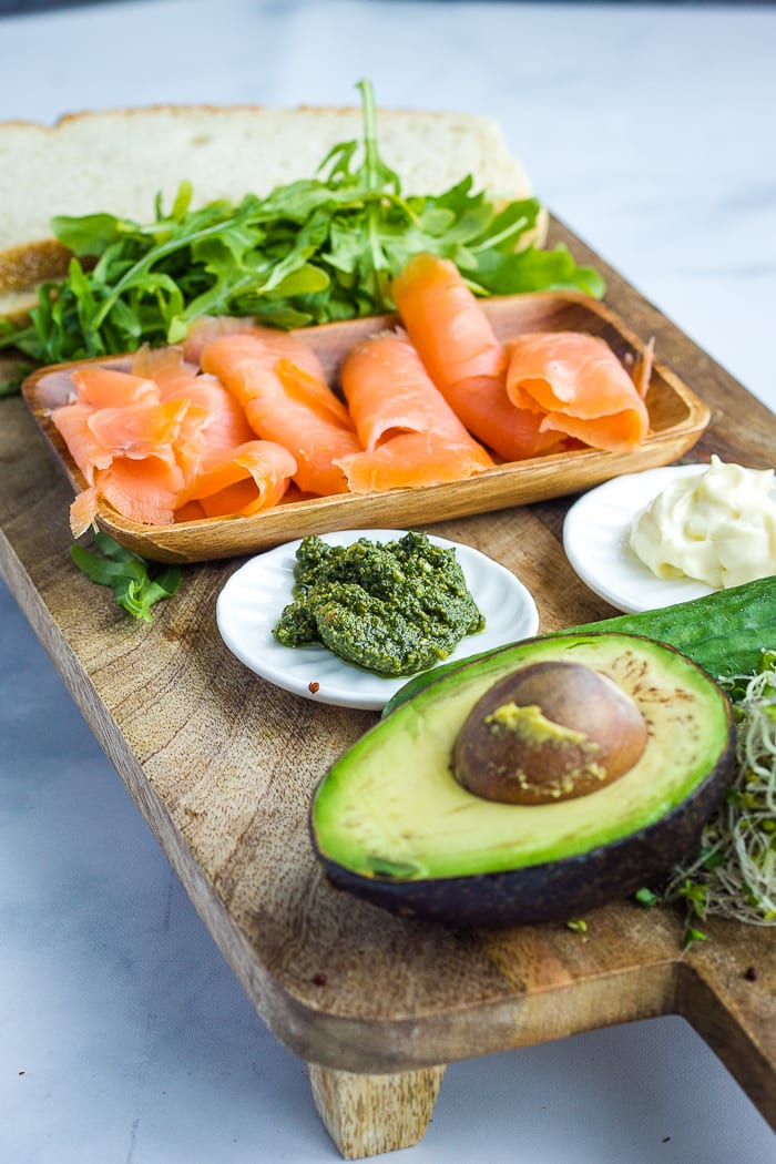 avocado, pesto, mayo, smoked salmon, arugula and bread on a cutting board