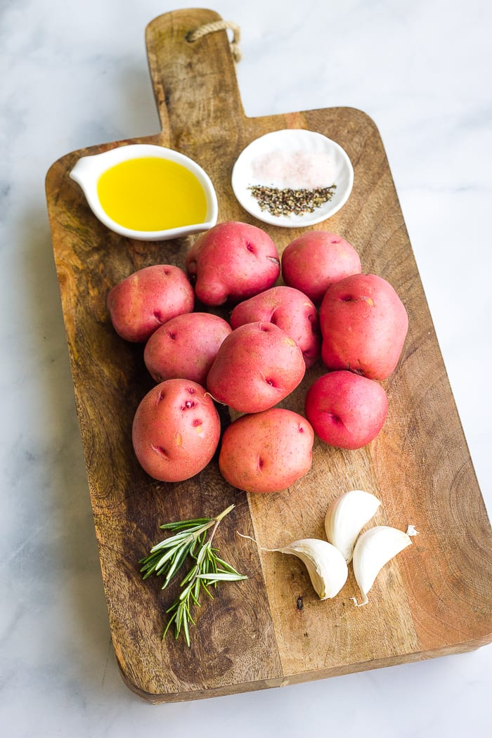 Ingredients for roasted potatoes on a cutting board