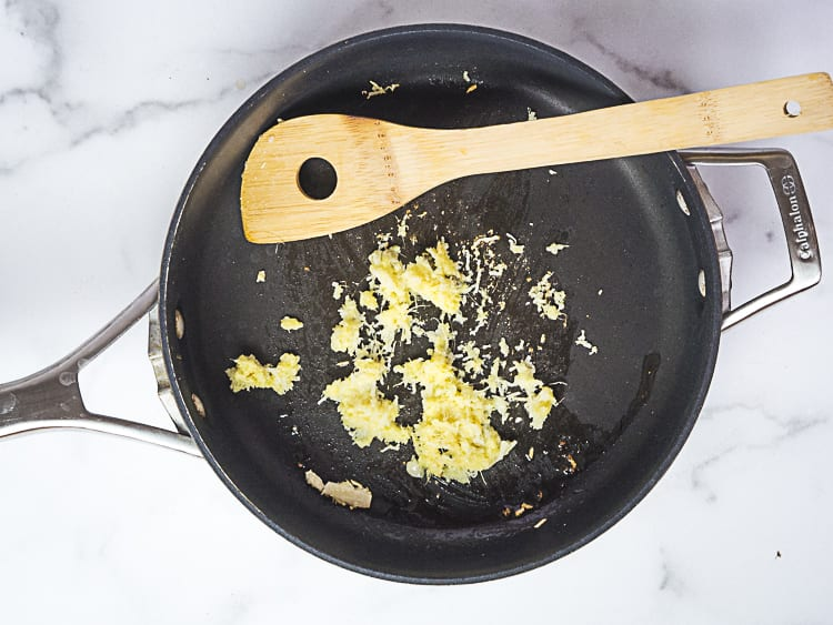 cooking minced ginger and garlic in a frying pan