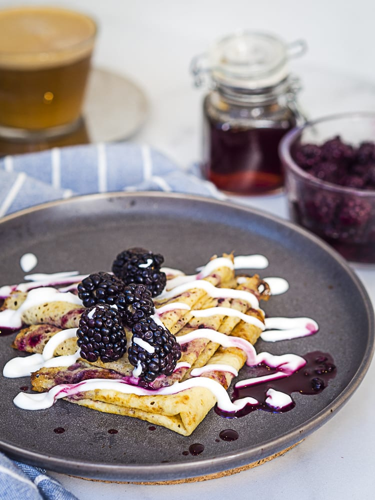 crepes topped with blackberries and yogurt drizzle