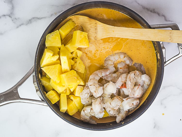 adding pineapple and shrimp to red curry